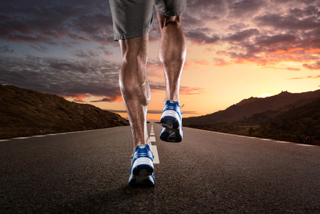 Close up of athlete running on the empty road at the sunset