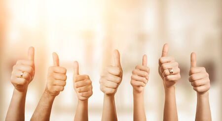 Photo pour Close up of group of hands showing thumbs up over defocused background with copy space - image libre de droit