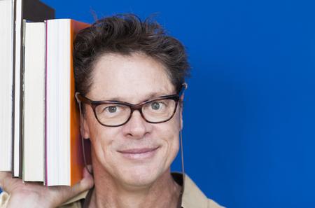 Foto de Teacher with glasses, happy with books in hand showing people - Imagen libre de derechos