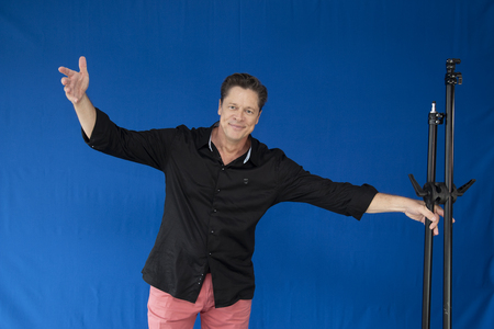 Foto de Photographer with open arms and tripe in hand, smiling - Imagen libre de derechos