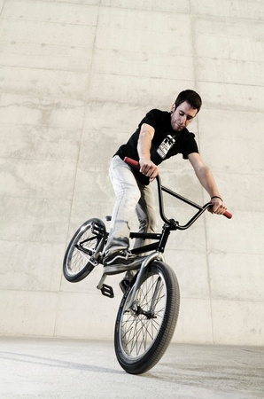 Young bicycle rider on a grey urban concrete background