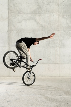 Young BMX bicycle rider on a grey urban concrete background