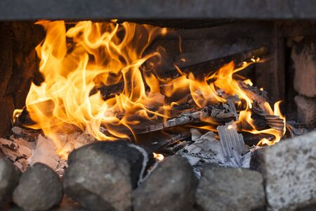 Photo for Close-up of the fire of a barbecue with burned firewood and ashes - Royalty Free Image