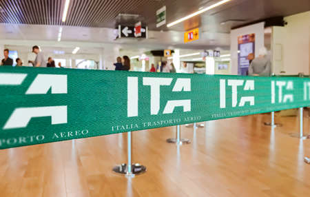 Foto per Fiumicino, Italy, July 2021: green ribbon barrier with the ITA airline logo inside the Leonardo da Vinci airport in Rome, Italy. ITA is the new Italian flag carrier starting from 15 October 2021 - Immagine Royalty Free