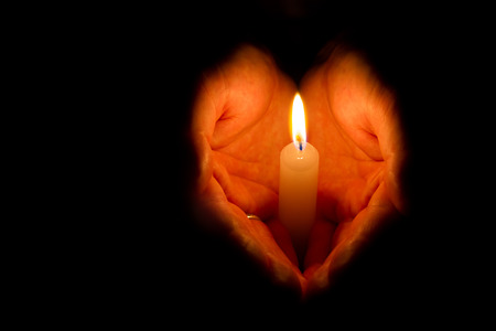 Photo for Man hands holding a burning candle on dark background - Royalty Free Image