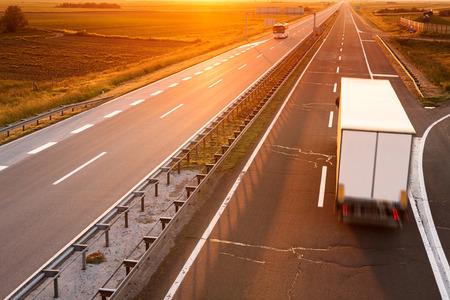 Foto de Truck and bus on highway in motion blur at sunset - Imagen libre de derechos