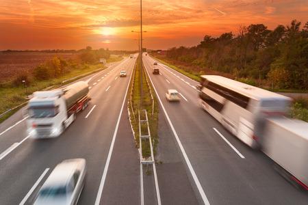 Foto de Truck and bus in motion blur on the highway towards the setting sun. Rush hour on the freeway near Belgrade - Serbia. - Imagen libre de derechos