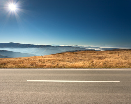 Foto de Side view of empty asphalt road and cloudy mountains in background at idyllic sunny day. - Imagen libre de derechos