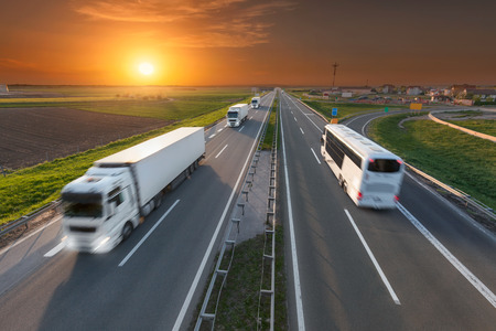 Photo pour Many white trucks in line and fast travel bus driving towards the sun. Speed blurred motion drive on the freeway at beautiful sunset. Transport travel scene on the motorway near Belgrade, Serbia. - image libre de droit