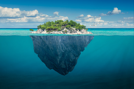 Foto de Beautiful underwater view of lone small island above and below the water surface in turquoise waters of tropical ocean. - Imagen libre de derechos