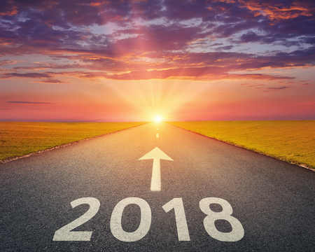 Foto de Driving on open road towards the setting sun to new year 2018. Concept for success and passing time. - Imagen libre de derechos
