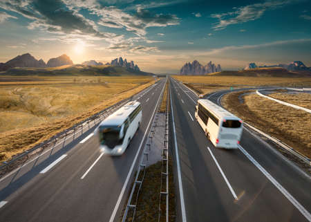 White buses driving towards the mountain range at beautiful sunset. Fast blurred motion drive on the straight freeway in beautiful landscape. Travel scene on the motorway.