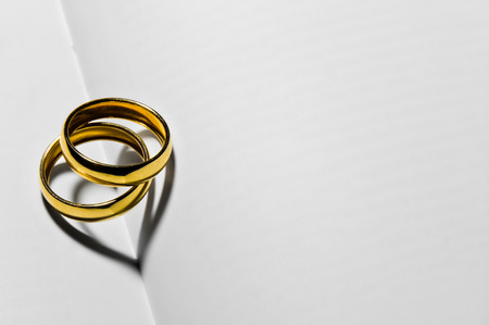 Photo for Close up of two wedding rings that create two hearts in heir shadow - Royalty Free Image