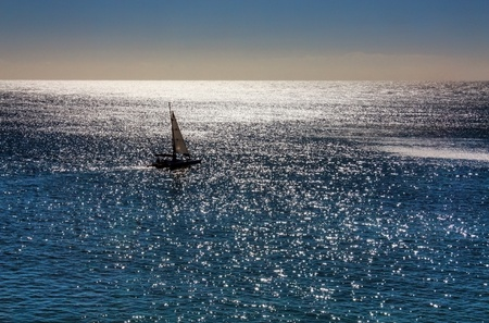 small sailing boat on turquoise ocean
