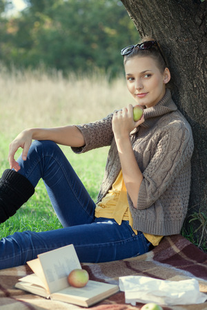 trendy girl have rest with a book in the park. eating an apple. sitting near the tree