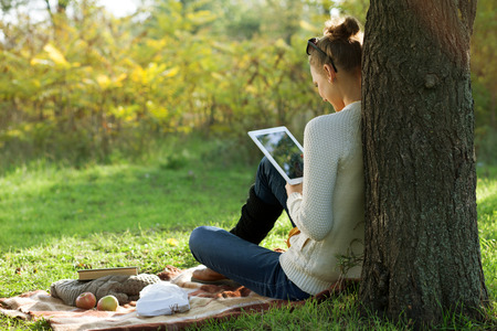 Distance education. Sitting woman using pad during stroll outdoors