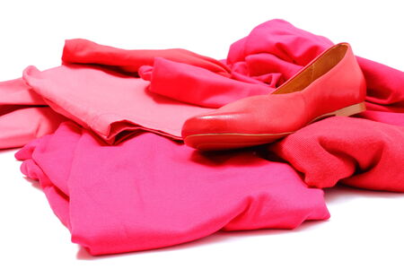 Heap of red and pink shirts and pants with womanly shoes, womanly clothes  Isolated on white background