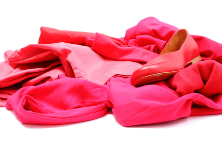 Heap of red and pink shirts and pants with womanly shoes, womanly clothes. Isolated on white background