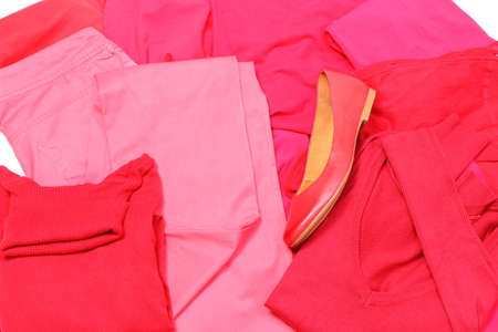 Heap of red and pink shirts and pants with womanly shoes, womanly clothes