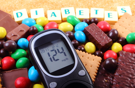 Glucose meter with word diabetes, heap of candies, cookies and brown cane sugar, too many sweets, unhealthy food, concept of diabetes and reduction of eating sweets