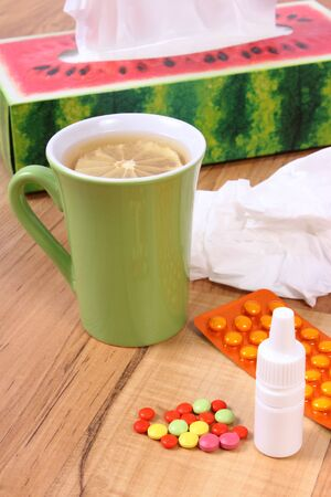 Pills and nose drops for colds, handkerchiefs and hot tea with lemon, treatment of colds, flu and runny