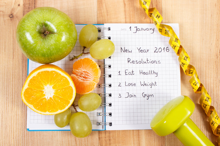 New years resolutions eat healthy, lose weight and join gym written in notebook, fresh fruits, dumbbells for fitness and tape measure, healthy lifestyle