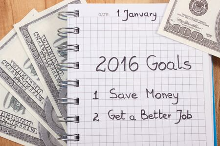 New years resolutions save money and get better job written in notebook and currencies dollar