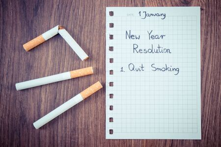 Vintage photo, New years resolutions quit smoking written on sheet of paper and broken cigarette, concept of healthy lifestyle, world no tobacco day