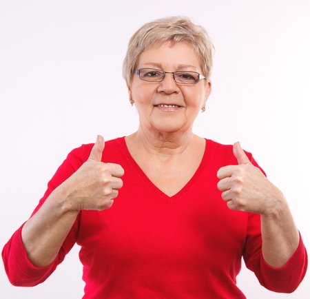 Photo pour Happy smiling elderly woman showing thumbs up, approval of offer or situation, showing positive human emotions, facial expressions - image libre de droit