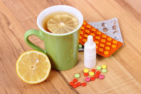 Pills, nose drops and hot tea with lemon for colds, treatment of colds, flu and runny