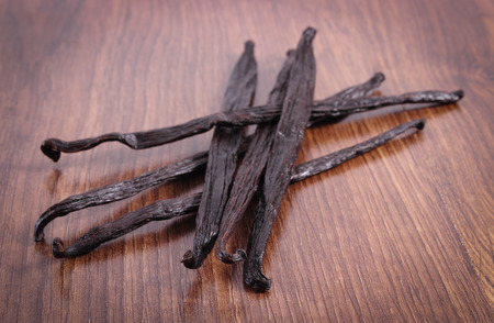 Photo for Fresh fragrant vanilla sticks pods on wooden surface plank, seasoning for cooking or baking - Royalty Free Image