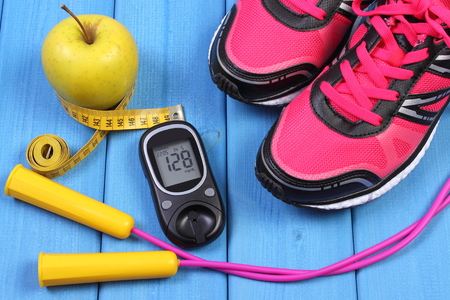 Glucose meter with result of sugar level, sport shoes, apple and accessories for fitness or sport, diabetes, healthy and active lifestyles