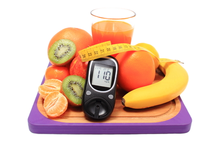 Glucose meter, fresh ripe natural fruits with tape measure and glass of juice on cutting board, concept for diabetes, healthy nutrition and strengthening immunity
