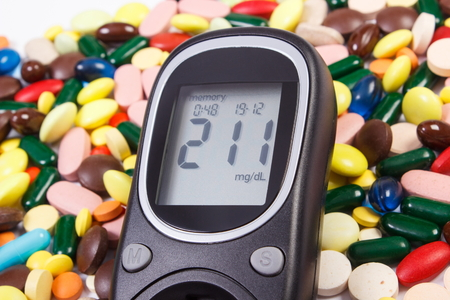 Glucose meter with result of measurement sugar level and heap of colorful medical pills, capsules or supplements for therapy, concept of treatment, diabetes and health care