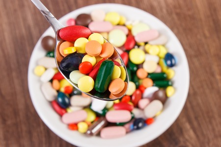 Colorful medical pills on teaspoon and capsules or supplements for therapy in background on plate, concept of treatment and health care