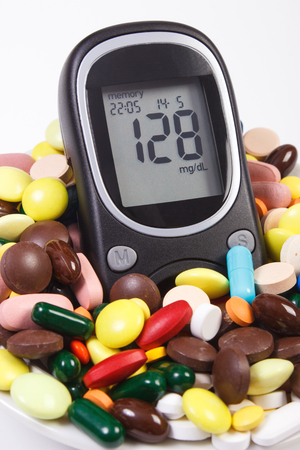 Glucose meter with result of measurement sugar level, colorful medical pills, capsules or supplements for therapy, treatment, diabetes and health care