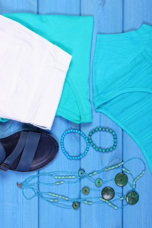 Clothing for woman and accessories for vacation or summer on blue boards, leather sandals, shirt, pants