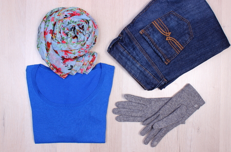Womanly clothes on wooden plank, gloves, sweater, shawl or scarf and pants, warm clothing for autumn or winter