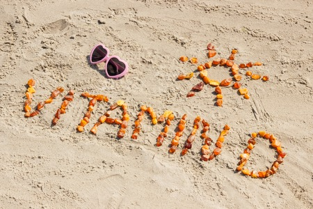 Photo pour Sunglasses, inscription vitamin D and shape of sun on sand at beach, concept of vacation time and prevention of vitamin D deficiency - image libre de droit