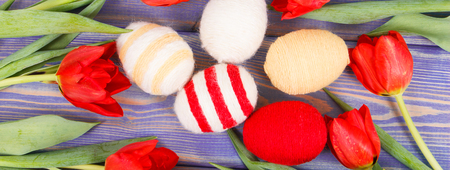Photo for Fresh red tulips and eggs wrapped woolen string on boards as festive Easter decoration - Royalty Free Image