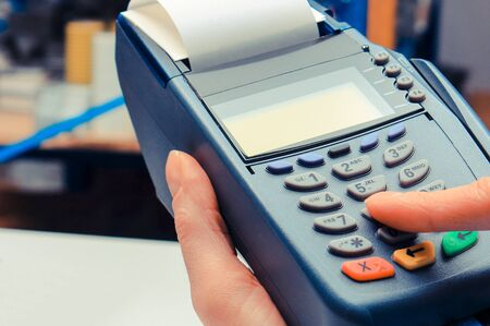Photo pour Hand of woman using payment terminal in electrical shop, paying with credit card, enter personal identification number - image libre de droit