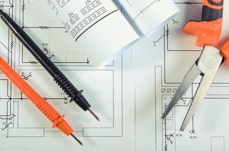 Foto de Cables of multimeter and pliers on construction drawings of house. Building home concept. Drawings for projects engineer jobs - Imagen libre de derechos