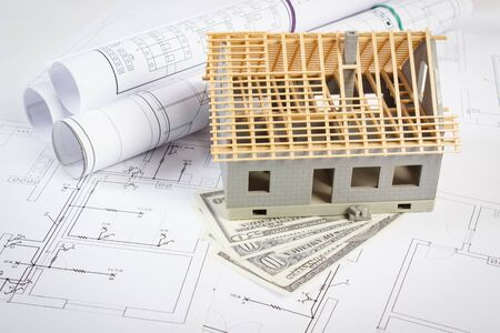 Photo pour Small house under construction and currencies dollar on electrical drawings and diagrams for project, concept of building home cost - image libre de droit