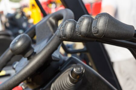 Photo pour Operating control panels or levers and steering wheel in forklift or other agricultural or industrial machine - image libre de droit