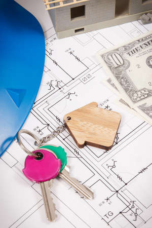 Photo pour Keys with home shape, currencies dollar and house under construction on electrical construction drawings for engineering jobs. Building or buying home concept. Technology - image libre de droit