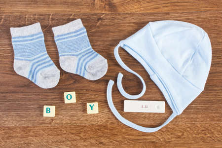 Photo pour Blue clothing for newborn baby with word boy and pregnancy test with positive result, concept of extending family and expecting for baby - image libre de droit