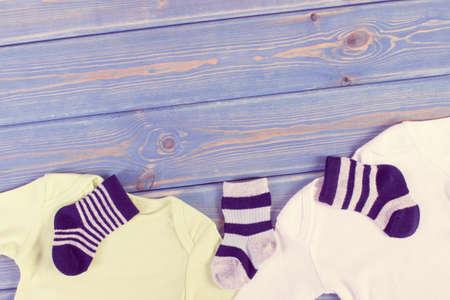 Photo pour Vintage photo. Clothes for little baby boy, extending family concept, copy space for text or inscription on blue boards - image libre de droit