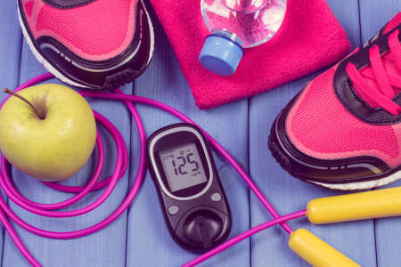 Foto de Glucose meter with result of sugar level, pair of sport shoes and accessories for fitness. Diabetes and healthy sporty lifestyles - Imagen libre de derechos
