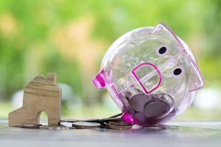Concept of saving and banking. Piggy bank and money coin near miniature house.