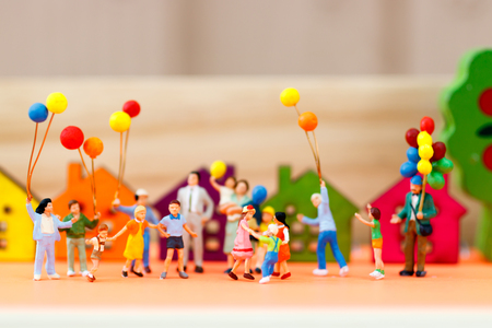 Photo pour Miniature people, family and children with colorful balloons standing in front of house, Family concept.  - image libre de droit